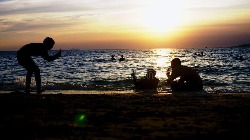 Een groep onherkenbare jongeren wordt gefotografeerd in het overzees op een zonsondergangachtergrond royalty-vrije stock afbeeldingen