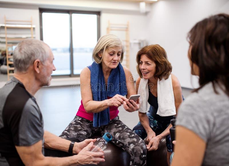 Een groep oudsten met smartphone in gymnastiek die na het doen van oefening rusten royalty-vrije stock afbeeldingen