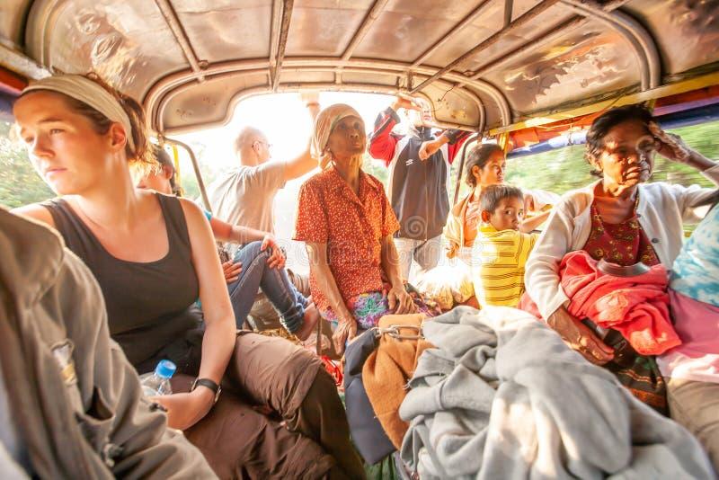 Een groep reizigers en plaatselijke bevolking in minibus op de weg aan grens Laos-Kambodja PAKSE, LAOS royalty-vrije stock foto's