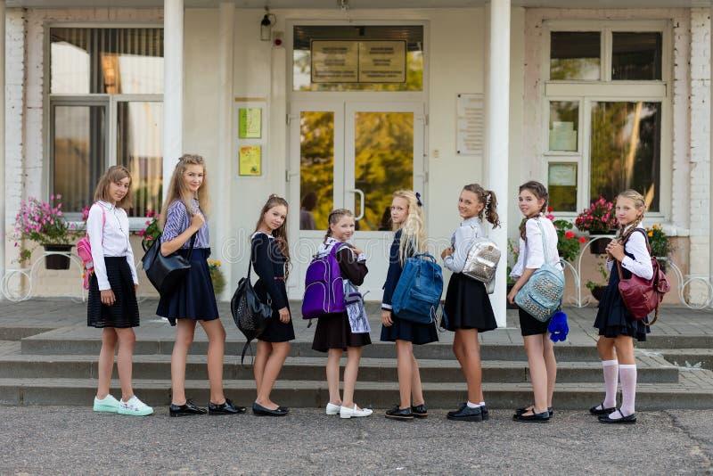 Een groep schoolmeisjes met rugzakken gaat naar school royalty-vrije stock fotografie