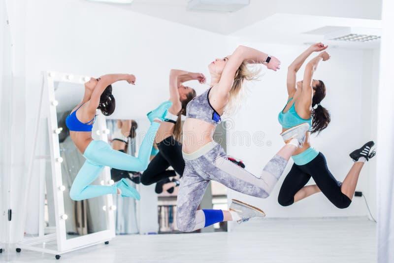 Een groep slanke geschikte atletische jonge vrouwen die gelijktijdige sprong in dansende studio doen stock fotografie