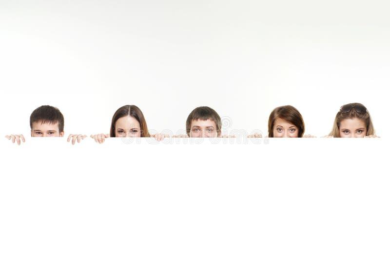 Een groep tieners die achter een witte banner verbergen stock afbeeldingen