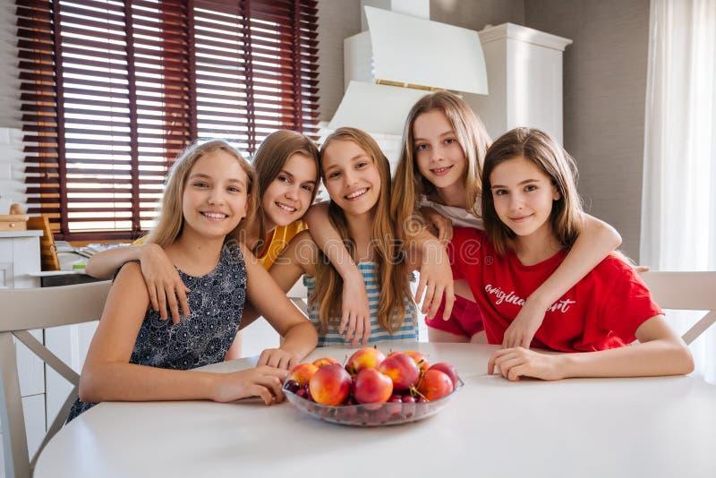Een groep tieners die in de keuken en het koesteren zitten royalty-vrije stock afbeelding
