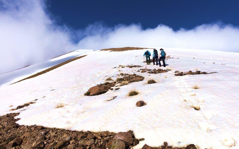 Een groep toeristen beklimt de rotsachtige snow-covered berghelling aan zijn mistige top royalty-vrije stock foto