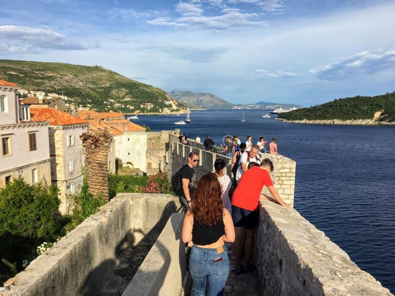 Een groep toeristen die de beroemde muren van Dubrovnik lopen, die de oude stad van Dubrovnik, Kroatië omringen royalty-vrije stock foto