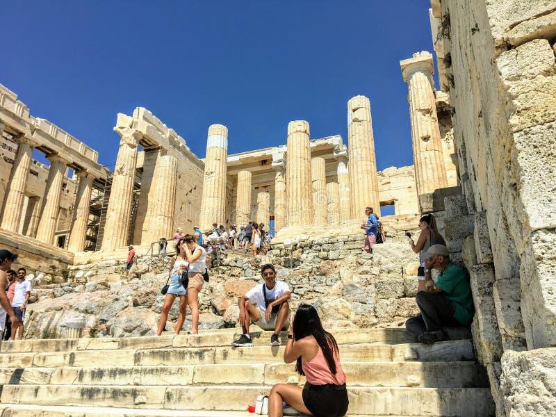 Een groep toeristen gaat en neemt beelden bij de ingang van de Akropolis in met oude Dorische kolommen wordt gevoerd die royalty-vrije stock fotografie
