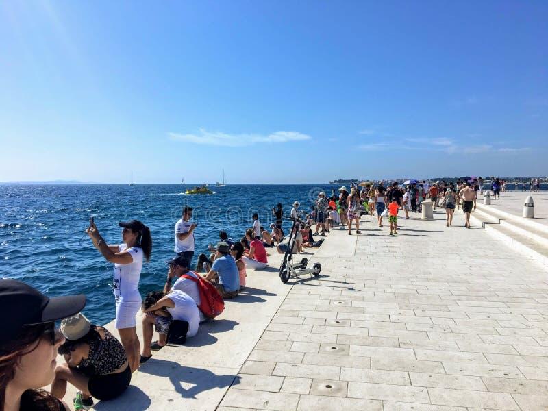 Een groep toeristen langs de waterkant in Oude Stad van Zadar, Kroatië naast de overzeese organen stock foto's