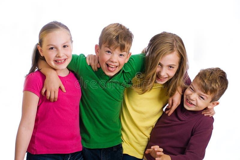 Een groep van vier jonge geitjes met kleurrijke overhemden. stock foto