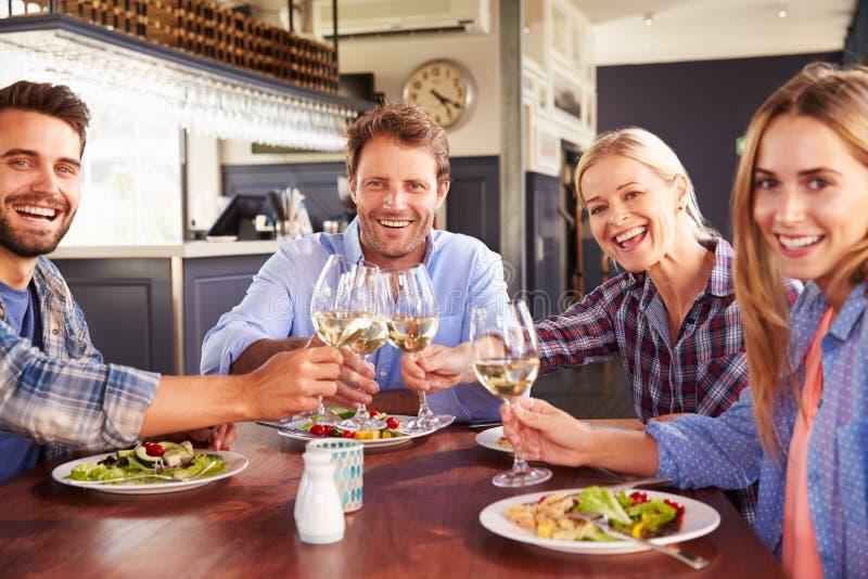 Een groep vrienden die een toost maken bij een restaurant, portret royalty-vrije stock foto