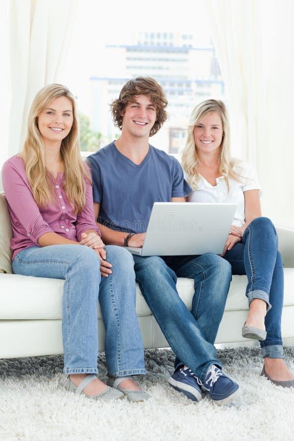Een Groep Vrienden Die Samen Zitten Aangezien Zij Laptop Gebruiken Royalty-vrije Stock Fotografie