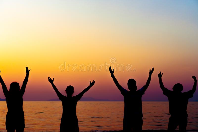 Een groep vrouwen neemt handen tot het concept van de hemelvrijheid met blauwe hemel en strandzonsondergang toe stock foto