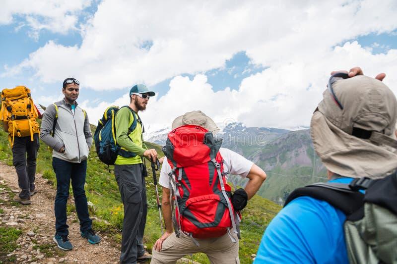 Een groep wandelaars met rugzakken en het volgen plakt rust en bevindt zich in de bergen luisterend aan hun gids royalty-vrije stock foto