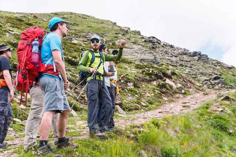 Een groep wandelaars met rugzakken en het volgen plakt rust en bevindt zich in de bergen luisterend aan hun gids stock afbeelding