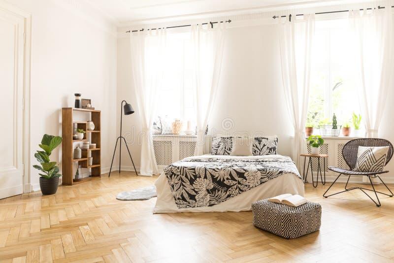 Een groot bed met linnen, een metaal en een rotanstoel, een lamp, een poef a stock foto