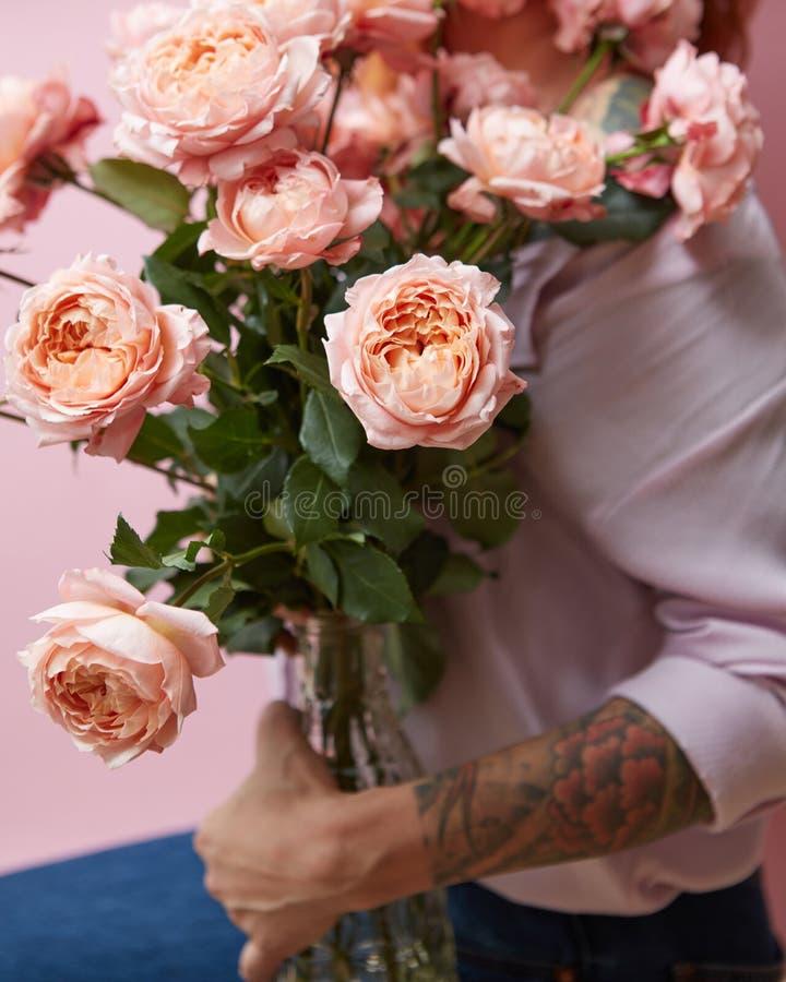 Een groot boeket van verse roze rozen in een glasvaas houdt een meisjesstandbeeld op een roze achtergrond De daggift van Valentin royalty-vrije stock afbeeldingen