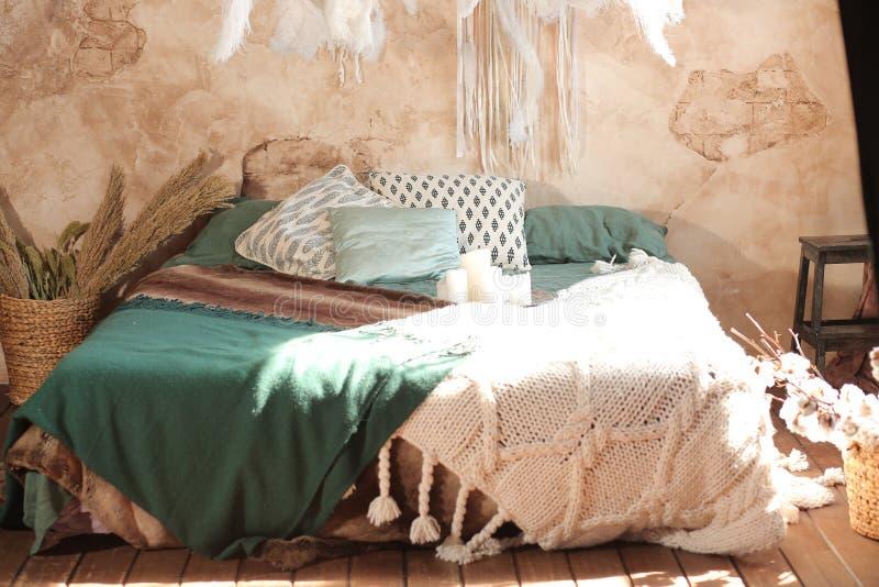 Een groot comfortabel bed in een heldere slaapkamer stock foto