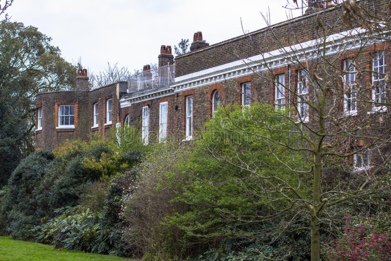Een groot Europees gebouw van de stijlbaksteen onder groene struiken en bomen stock foto's