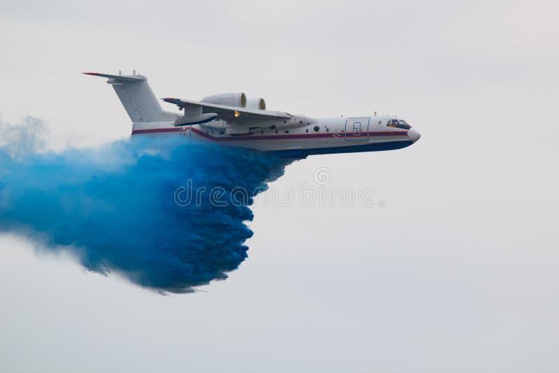 Een groot reddingsvliegtuig dumpt water om een brand te doven stock foto