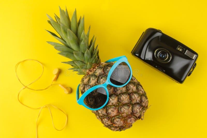 Een groot rijp ananasfruit in zonnescherm en cameraglazen op een heldere gele achtergrond De zomer Hoogste mening stock afbeeldingen