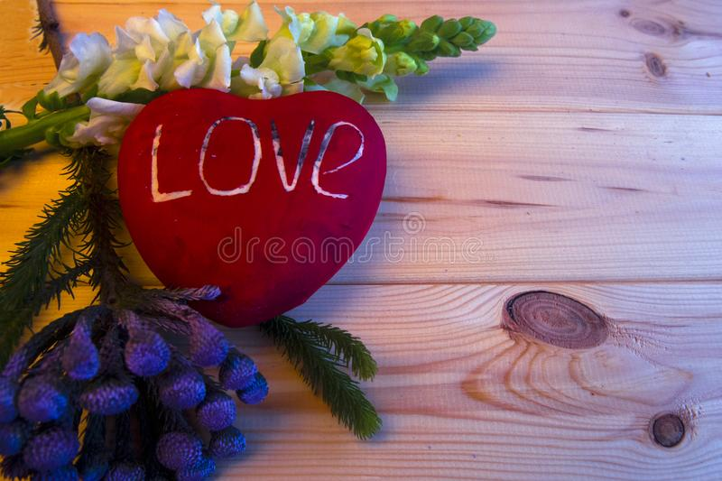 Een groot rood hart met de geschreven woordliefde ligt op een houten achtergrond royalty-vrije stock foto