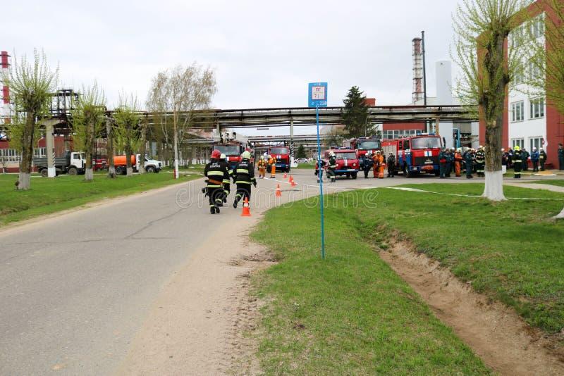 Een groot rood voertuig van de brandredding, een vrachtwagen om een brand en mannelijke brandbestrijders bij een chemisch product royalty-vrije stock afbeeldingen
