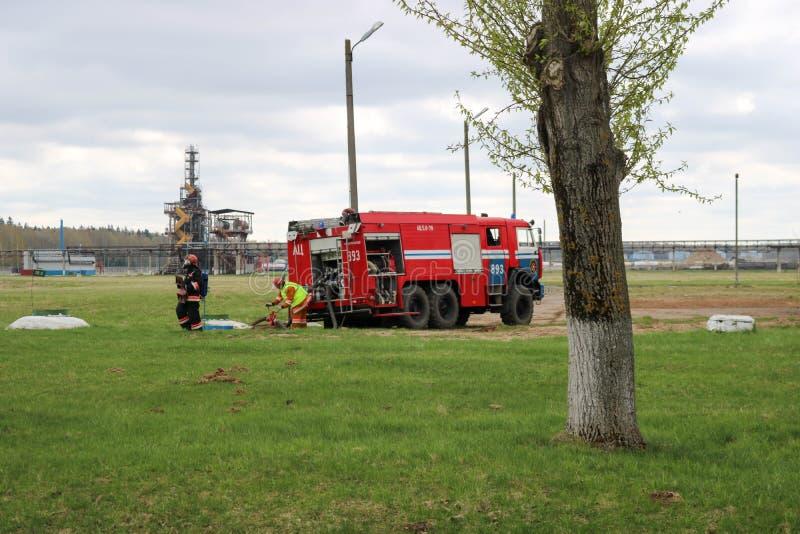 Een groot rood voertuig van de brandredding, een vrachtwagen om een brand en mannelijke brandbestrijders bij een chemisch product stock foto