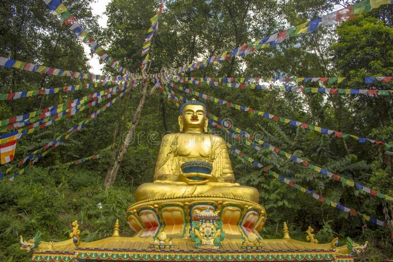 Een groot standbeeld van een gouden zitting Boedha in een groene bos en multicolored gebedvlaggen van Tibet boven hem royalty-vrije stock fotografie