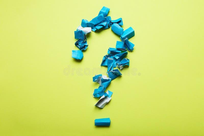 Een groot vraagteken van stukken van verfrommeld blauw document op een gele achtergrond stock fotografie