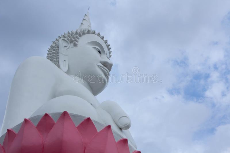 Een groot wit beeld van Boedha met een bewolkte hemel houdt van kalmte steek stock foto's