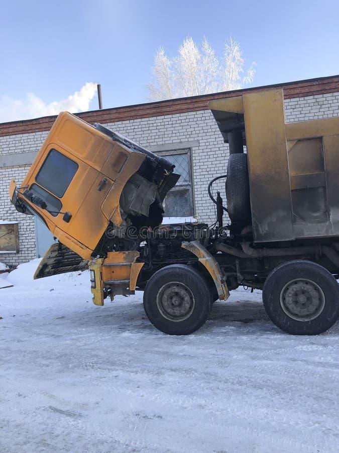 Een grote carrière vuile vrachtwagen stond voor de winterreparaties op op de straat De vrachtwagen van de cabinestortplaats wordt stock afbeeldingen