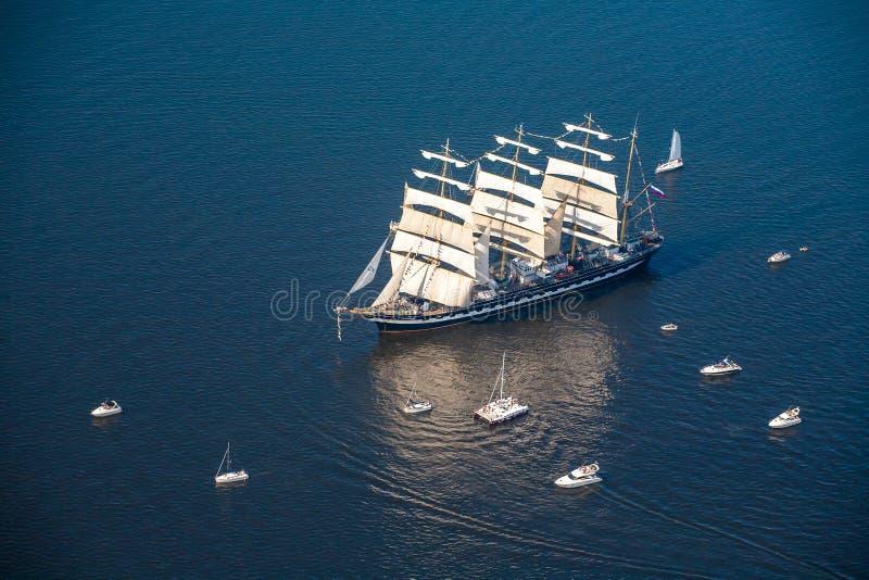 Een grote die zeilboot, schors gaat in het overzees door vele jachten wordt omringd nThe laatste windjammerschors Kruzenstern stock foto's