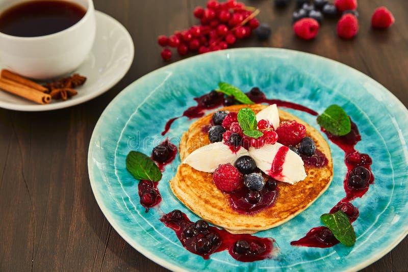 Een grote eigengemaakte pannekoek met witte mascarponeroom, frambozen, bosbessen, bessen, bessen en honing op een blauwe plaat He royalty-vrije stock afbeelding