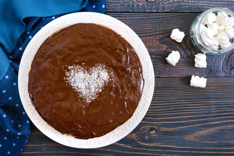 Een grote feestelijke chocoladecake, een hart van kokosnoot in het midden stock afbeeldingen