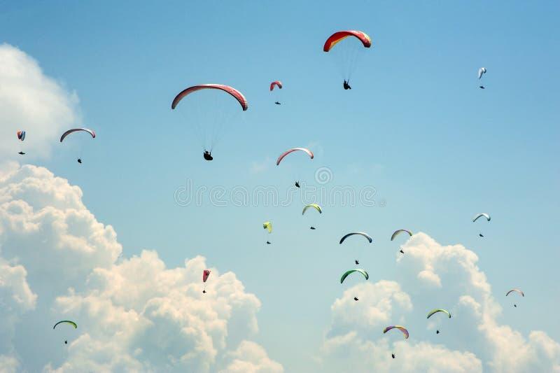 Een grote groep glijschermen vliegt in de hemel tegen de achtergrond van wolken stock afbeelding