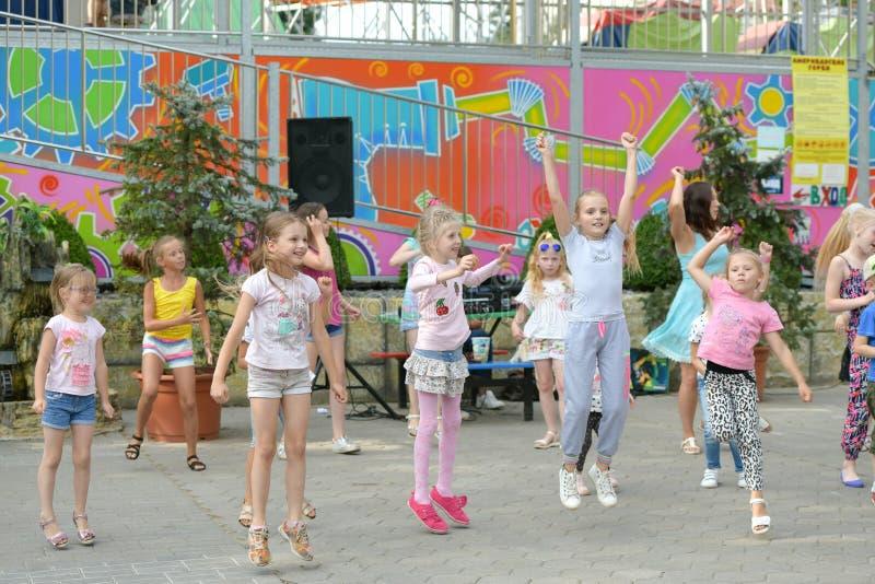 Een grote groep het gelukkige de jonge geitjes van pretsporten springen, sporten en het dansen Kinderjaren, vrijheid, geluk, het  stock foto's
