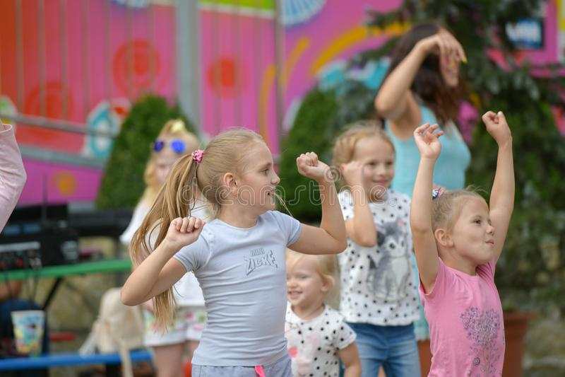 Een grote groep het gelukkige de jonge geitjes van pretsporten springen, sporten en het dansen Kinderjaren, vrijheid, geluk, het  stock fotografie