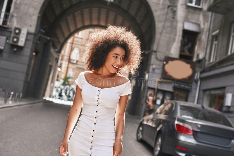 In een grote haast De mooie en jonge Amerikaanse vrouw die van Afro in plotseling witte kleding terwijl in openlucht status gliml stock fotografie