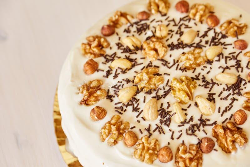 Een grote heerlijke pastei met okkernoten Eigengemaakte pastei met wit bovenste laagje en chocoladeschilfers op een witte houten  royalty-vrije stock foto