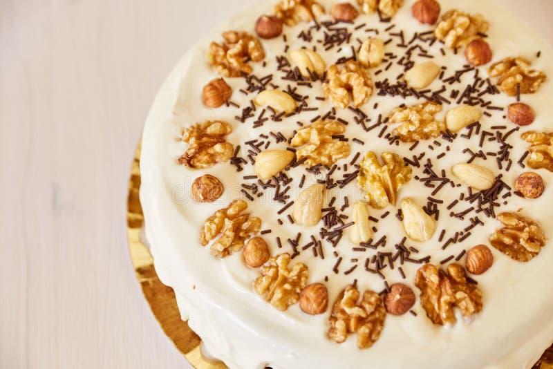 Een grote heerlijke pastei met okkernoten Eigengemaakte pastei met wit bovenste laagje en chocoladeschilfers op een witte houten  stock afbeeldingen