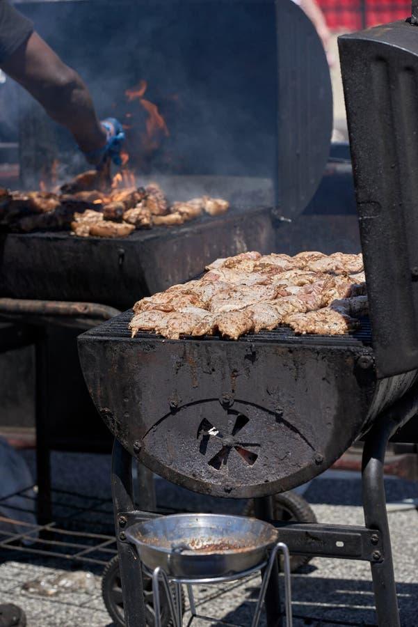Een grote houtskoolgrill met van gemarineerde kip met een vleesgrill op de achtergrond royalty-vrije stock fotografie
