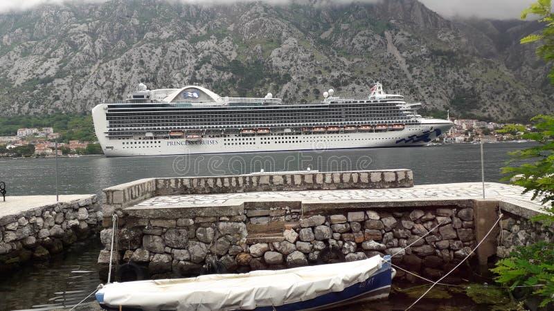 Een grote kruiser in de Kotor-baai op een kanaal gebaad in het licht van de zon stock afbeelding