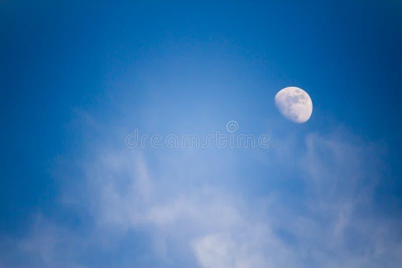 Een grote maan in de middag tegen een blauwe hemel met wolken stock afbeeldingen