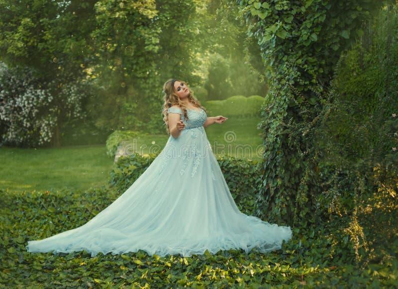 Een grote, mooie, jonge vrouw in een luxueuze blauwe kleding met een lange trein loopt in een bloeiende tuin Het model stock afbeelding