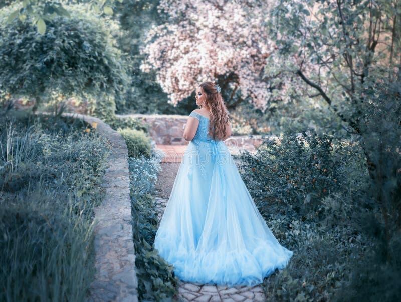 Een grote, mooie, jonge vrouw in een luxueuze blauwe kleding met een lange trein loopt in een bloeiende tuin Het model stock afbeeldingen