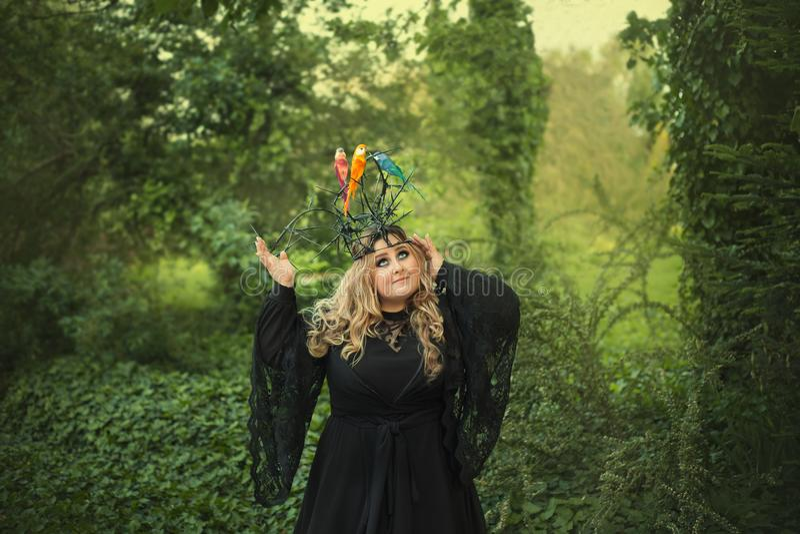 Een grote, mooie, jonge vrouw in een zwarte kleding en in een kroon met doornen waarop de vogels zitting-golvende papegaaien zijn royalty-vrije stock afbeelding