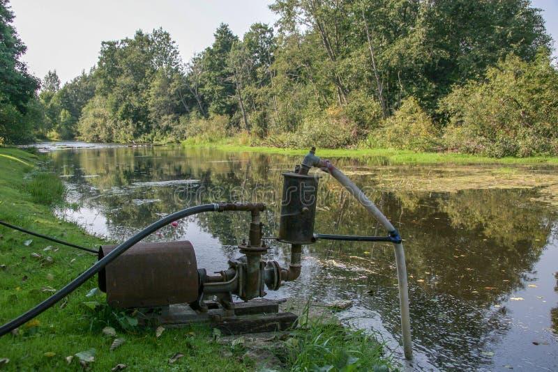Een grote oude waterpomp bevindt zich op de bank van de rivier en het pompenwater royalty-vrije stock foto