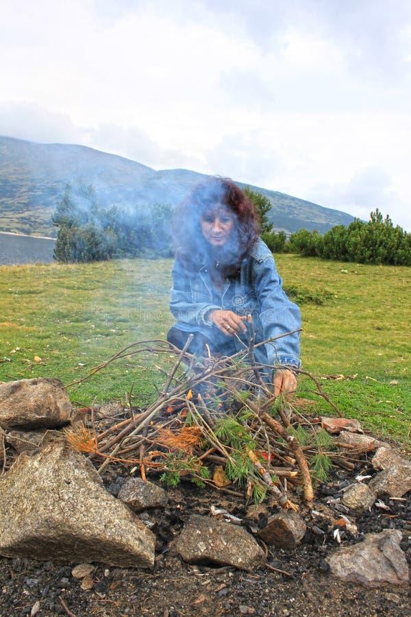 Een grote picknickbrand in het hout en een vrouw dichtbij het royalty-vrije stock foto