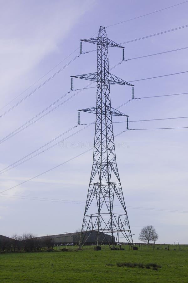 Een grote pyloon en kabels die die elektriciteit dragen bij Ballylumford-Macht Stationy in het net wordt geproduceerd stock foto