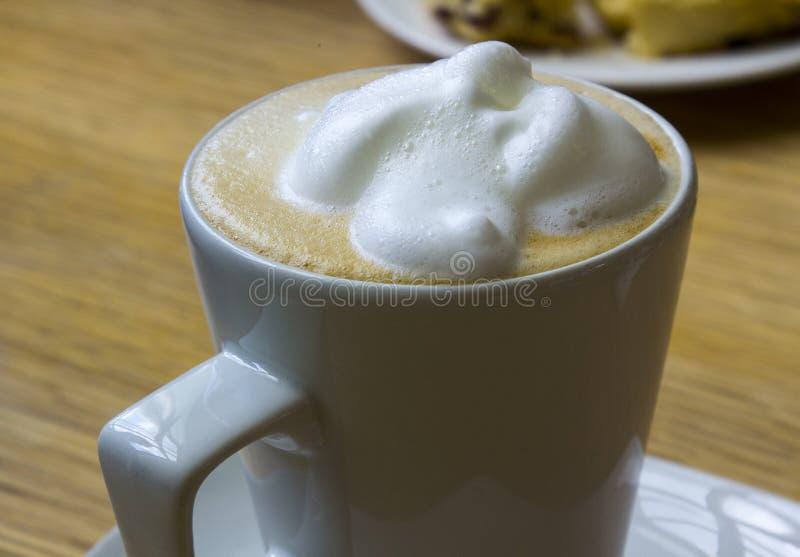 Een grote schuimende bedekte hete cappuccinokoffie in een duidelijke porseleinkop royalty-vrije stock foto