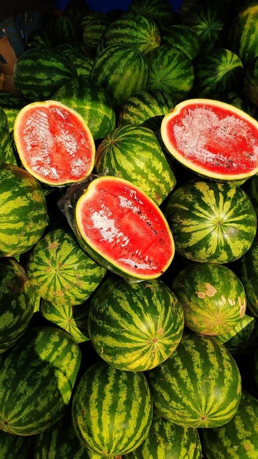 Een grote stapel van groene gestreepte watermeloenen, een marktbank voor een watermeloenhandelaar, besnoeiings rode watermeloenen stock foto's